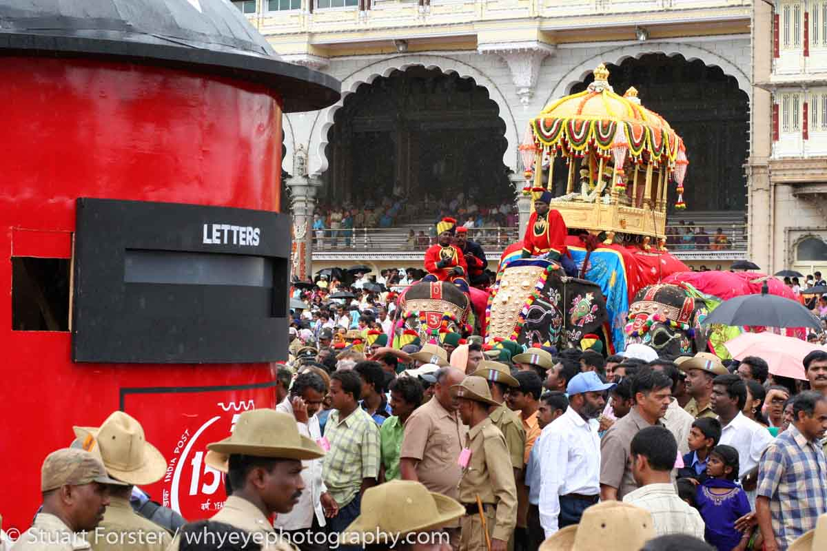 Caparisoned elephants stand at the Dasara procession in Mysore, India. A model of a letterbox is pulled. The procession starts from the Amba Vilas Palace (also known as Mysore Palace) on the tenth and final day of the Dasara Festival. The Procession led by an elephant carrying a golden howdah winds through the streets of the city and ends at Banni Mantap. Groups of performers, musicians and artists from around Karnataka participate in the celebration. The Dasara festivities can be traced back to the Puranas. The very first Dasara in the history of Mysore state can be traced back to the Mahnavami of the Raja Wadiyar in 1610, celebrated at Sriranapatnam. The celebrations honour the victory of the Hindu godess Chamundeswari over the buffalo headed demon Mahishasura.