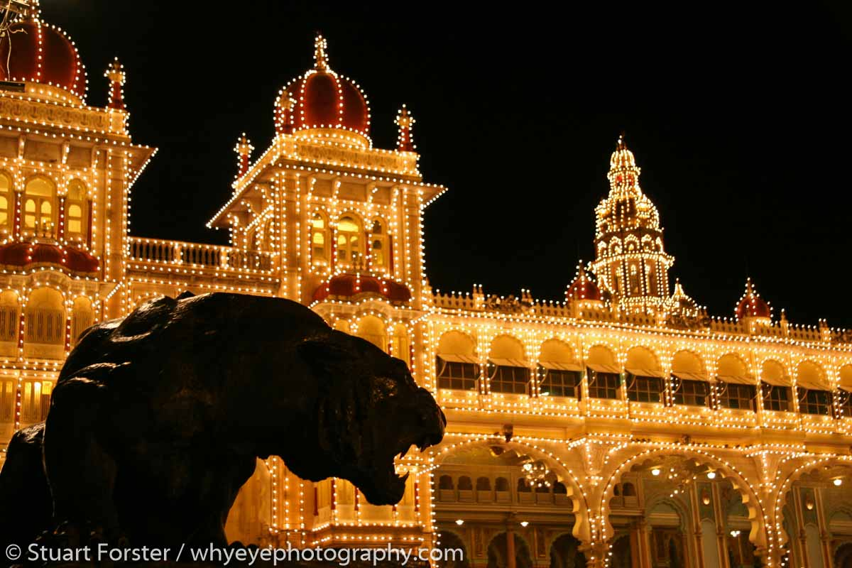 A tiger statue is silhouetted in front of illuminations at Mysore Palace, Mysore, Karnataka.