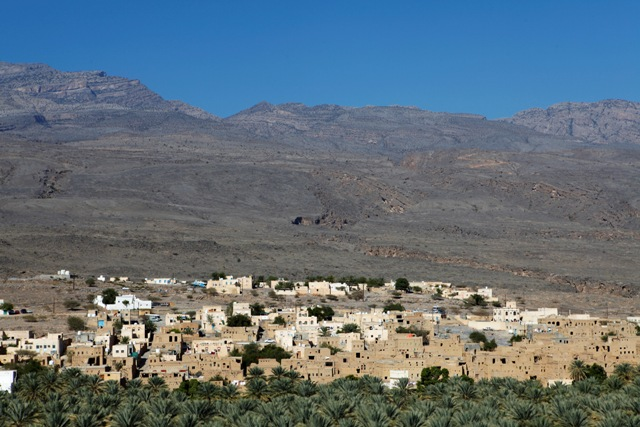 "The red, earth coloured houses of the Omani village of Al Hamra. Al Hamra, close to Nizwa, has no defences and is surrounded by lush plantations, thanks to a system of ""falaj"" irrigation canals"